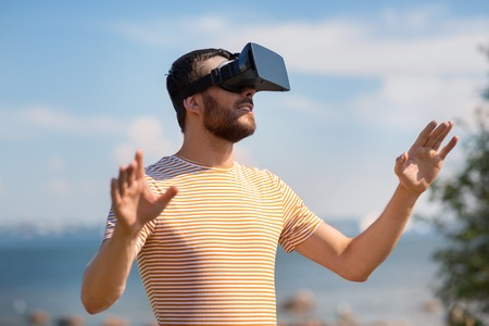technology, virtual reality, entertainment and people concept - young man with vr headset or 3d glasses playing video game outdoors Stock Photo