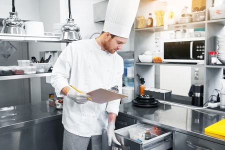 chef with clipboard doing inventory at kitchen