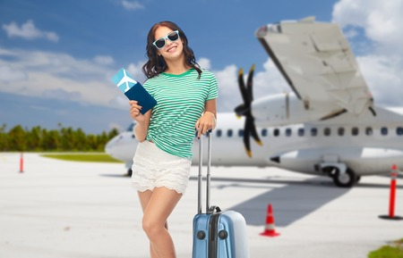teenage girl with travel bag and airplane ticket