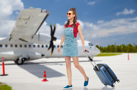 teenage girl with travel bag over airfield