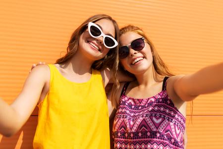 teenage girls taking selfie outdoors in summer