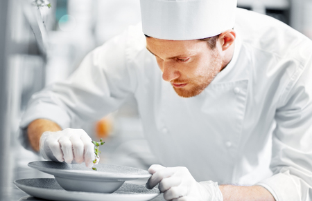 gelukkige mannelijke chef-kok die voedsel kookt bij restaurantkeuken