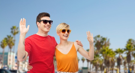 couple in sunglasses hugging and waving hands