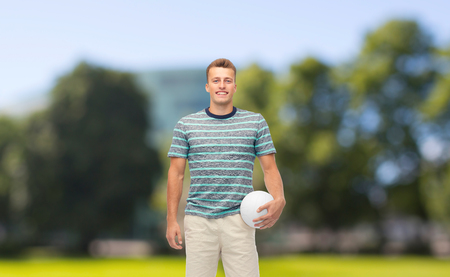 smiling young man with volleyball over summer par