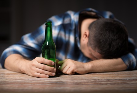 drunk man with beer bottles on table at night