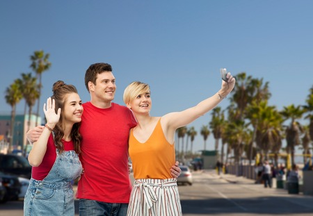 friends taking selfie by smartphone and hugging