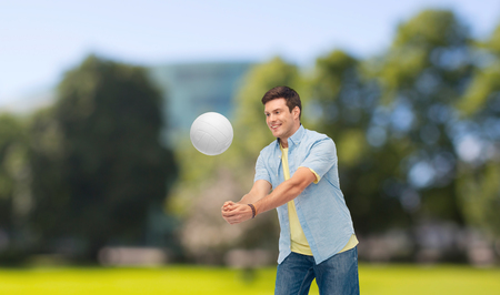 smiling man playing volleyball over summer par
