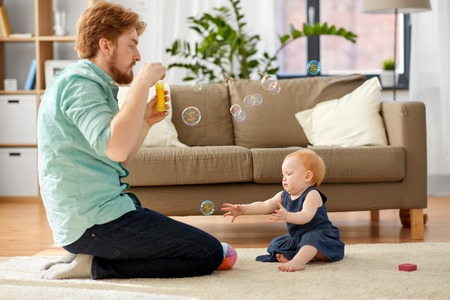 father and baby daughter with soap bubbles at home Stock Photo
