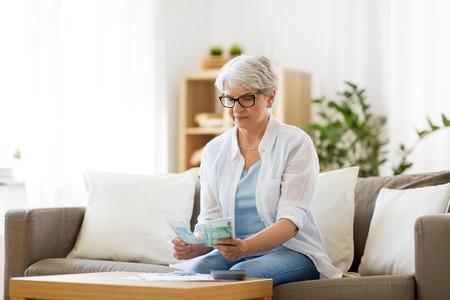 senior vrouw geld thuis tellen