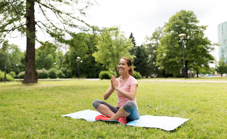 happy woman meditating in summer park