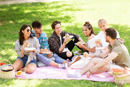 happy friends eating sandwiches at summer picnic