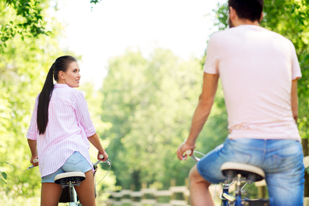 happy couple with bicycles at summer park