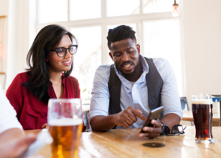 leisure, technology and people concept - happy man and woman with smartphones and drinks at bar or restaurant Stock Photo