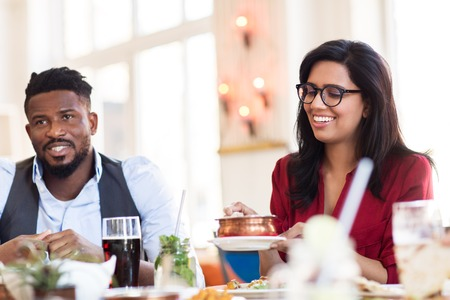 leisure, food and people concept - happy man and woman eating at restaurant