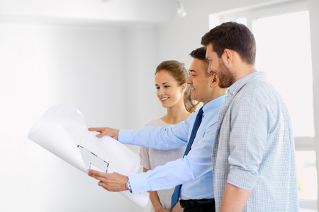 mortgage, people and real estate concept - realtor showing blueprint of new home to happy couple