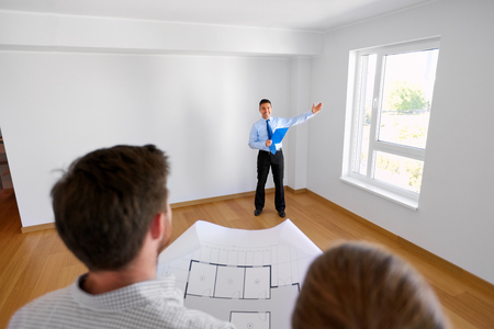 mortgage, people and real estate concept - happy realtor showing window at new home to couple with blueprint Stock Photo