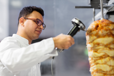 fast food and cooking concept - chef slicing doner meat from rotating spit at kebab shop Archivio Fotografico - 107221235