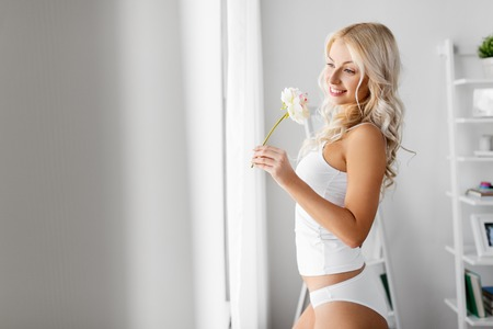 woman in underwear with peony flower at window