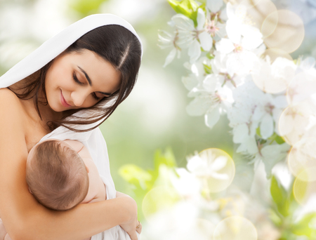 mother feeding baby over cherry blossoms