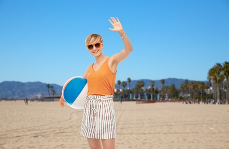 smiling teenage girl with ball over venice beach Stock Photo