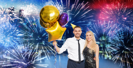 couple with party caps and balloons over firework