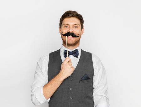 glücklicher junger Mann mit falschem Schnurrbart