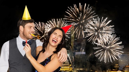 birthday, celebration and holidays concept - happy couple with party blowers and caps having fun over firework lights at night city background Stock Photo