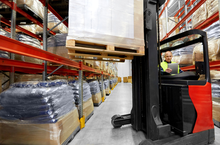 logistic business, shipment and loading concept - loader with tablet pc computer and cargo on forklift at warehouse Stock Photo