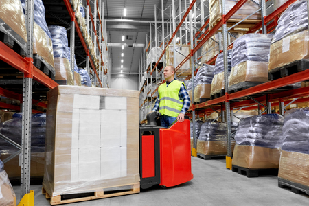 logistic business, shipment and loading concept - loader operating forklift with cargo at warehouse Reklamní fotografie