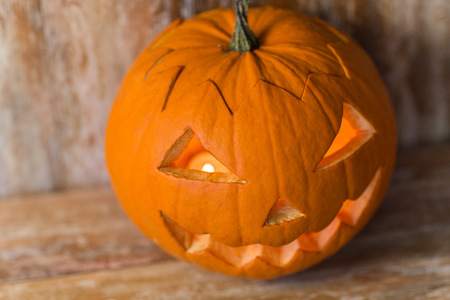 halloween, holidays and decoration concept - jack-o-lantern or carved pumpkin on wooden table at home