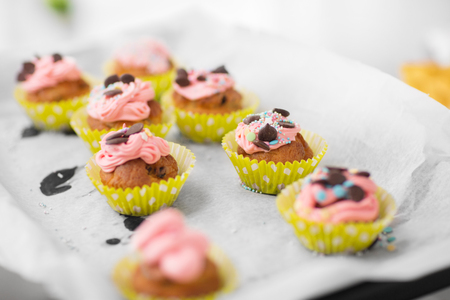 food, bakery and eating concept - close up of frosted cupcakes or muffins on oven tray