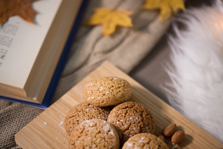 hygge, food and baking concept - oatmeal cookies on wooden board at home Фото со стока