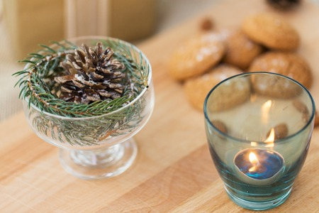 christmas concept - decoration of fir twig with pinecone in ice cream glass or dessert bowl and candle in holder
