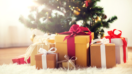 holidays, presents, new year and celebration concept - gift boxes on sheepskin at christmas tree
