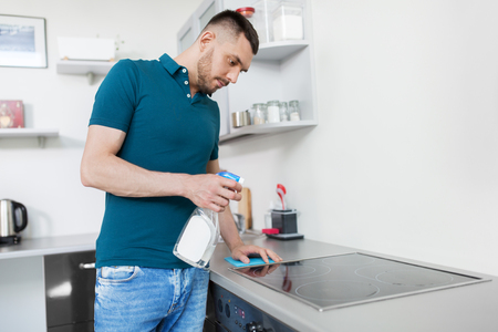 man with rag cleaning cooker at home kitchen Stock Photo