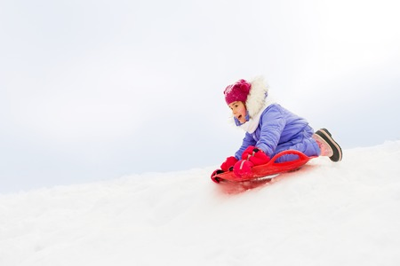 girl sliding down on snow saucer sled in winter Фото со стока