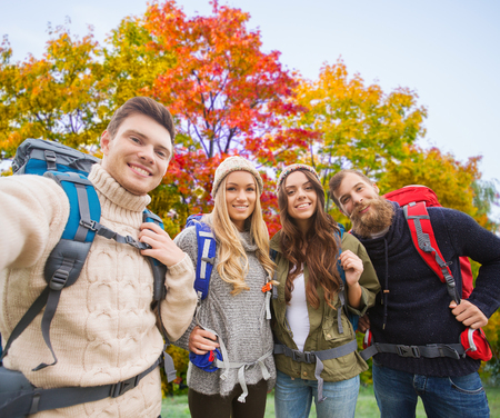 friends with backpacks taking selfie in autumn