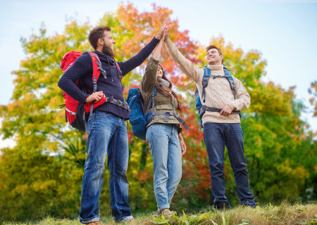 friends hiking and making high five in autumn