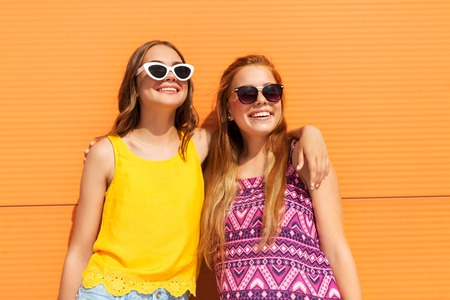 teenage girls in summer clothes hugging outdoors