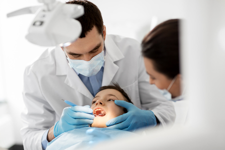 dentist checking for kid teeth at dental clinic