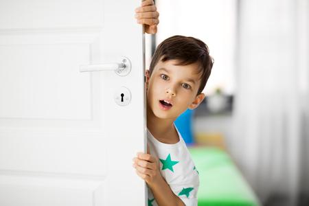 überraschter kleiner Junge hinter der Tür zu Hause
