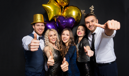 friends at christmas party showing thumbs up Stock Photo