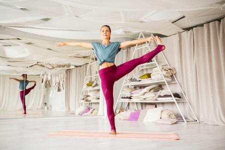 woman doing yoga hand-to-big-toe pose at studio