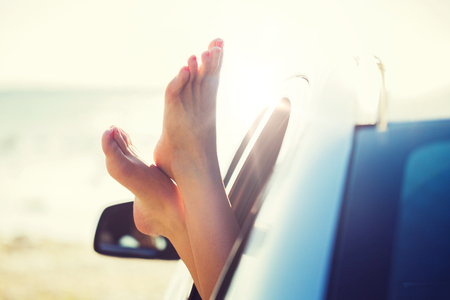 close up of woman feet showing from car window Stockfoto
