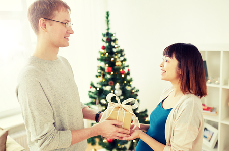 husband giving christmas present to pregnant wife Stock Photo