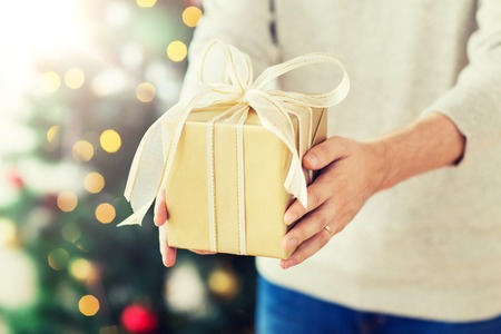 close up of man with christmas gift at home