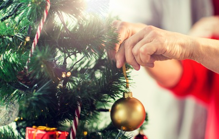 holidays and people concept - close up of happy senior woman decorating christmas tree Foto de archivo