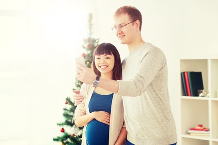 winter holidays, technology and people concept - happy husband and his pregnant wife taking selfie by smartphone home at christmas
