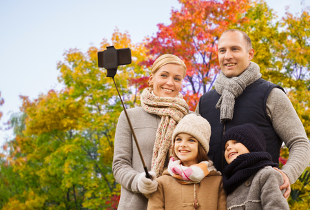 family taking selfie over autumn park background Stockfoto
