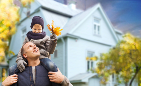 father and son with autumn maple leaves over house 写真素材